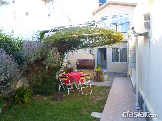 Pasillo de ingreso con mesa y sillas de  jardín y parrilla tambor